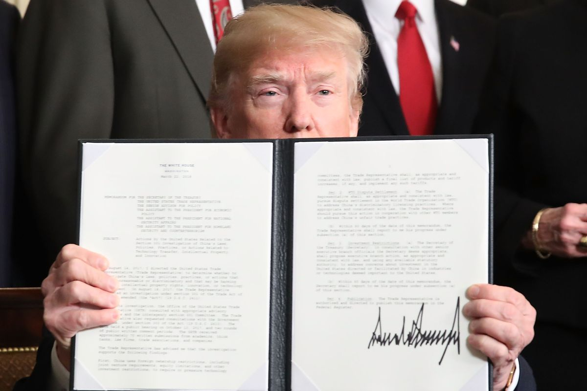President Donald Trump holds up a signed presidential memorandum aimed at what he calls Chinese economic aggression in the Roosevelt Room at the White House on March 22, 2018, in Washington, D.C.