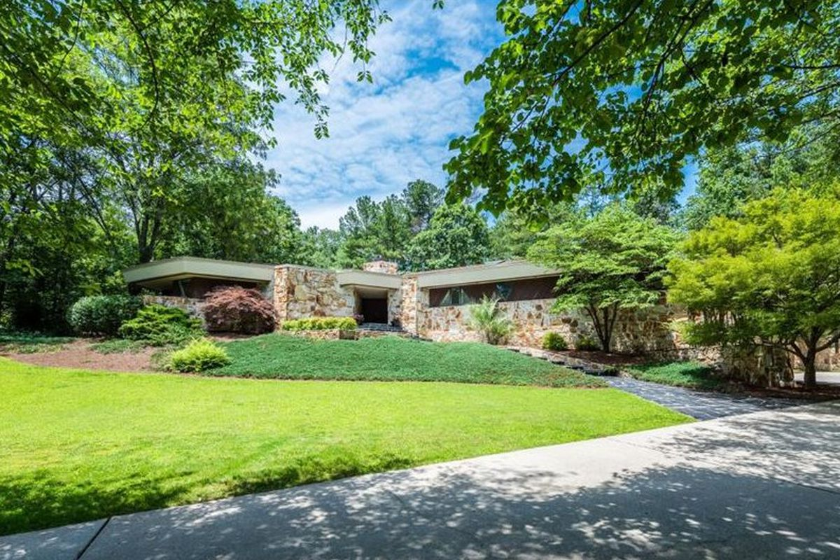 Landscaped yard leads to a stone house.