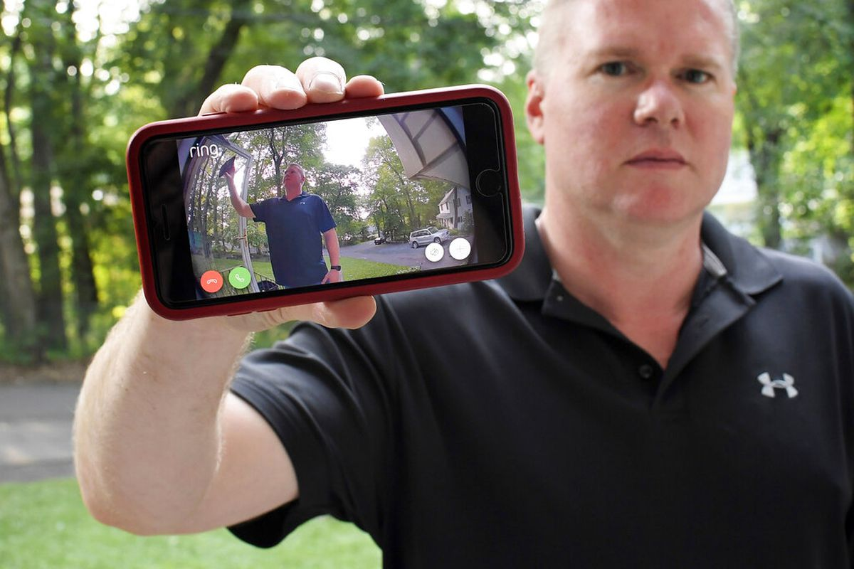 Man holds up live video of himself on his phone in front of his doorbell camera