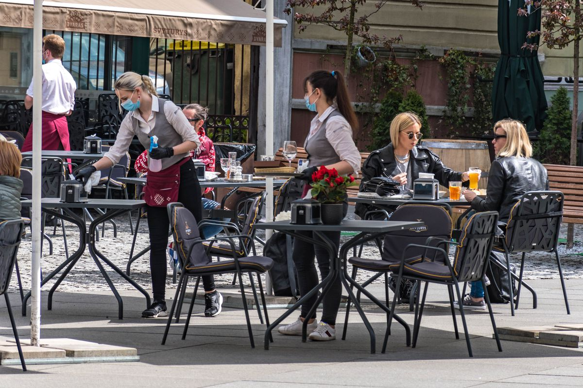 Waitresses with a mask and gloves disinfecting the table of an outdoor bar, café or restaurant with blonde girls at the table