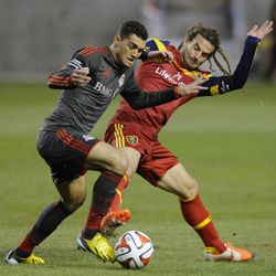 Real Salt Lake midfielder Kyle Beckerman (5) fights for control of the ball with Toronto FC forward Gilberto Oliveira Souza Junior (9) during a game at Rio Tinto Stadium in Sandy on Saturday, March 29, 2014.