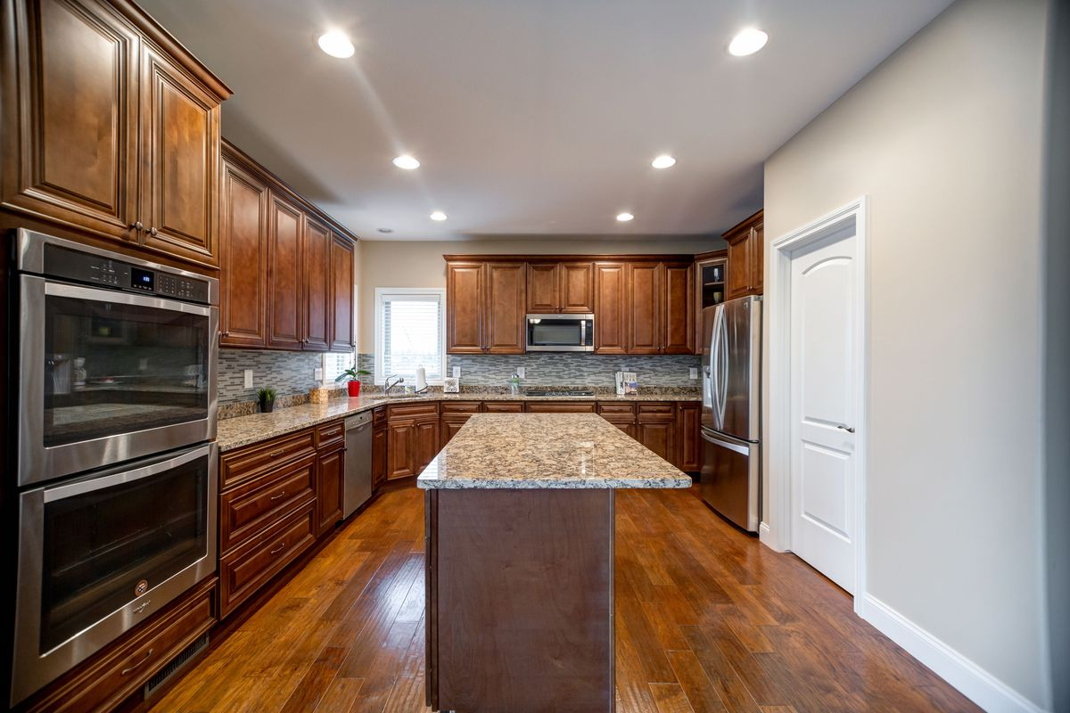 Kitchen with granite countertops, hardwood floors, and new appliances.