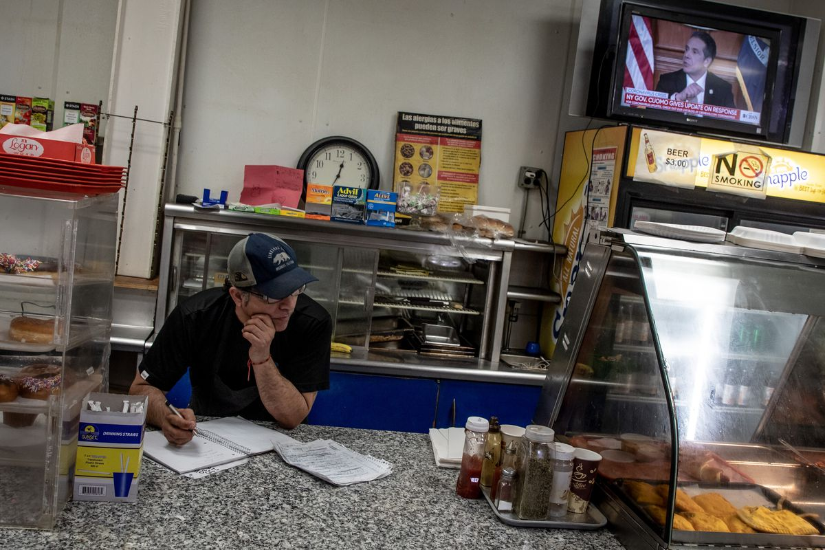 Carlos Sanchez makes notes of customer debts in his restaurant as Governor Andrew Cuomo is seen on TV.
