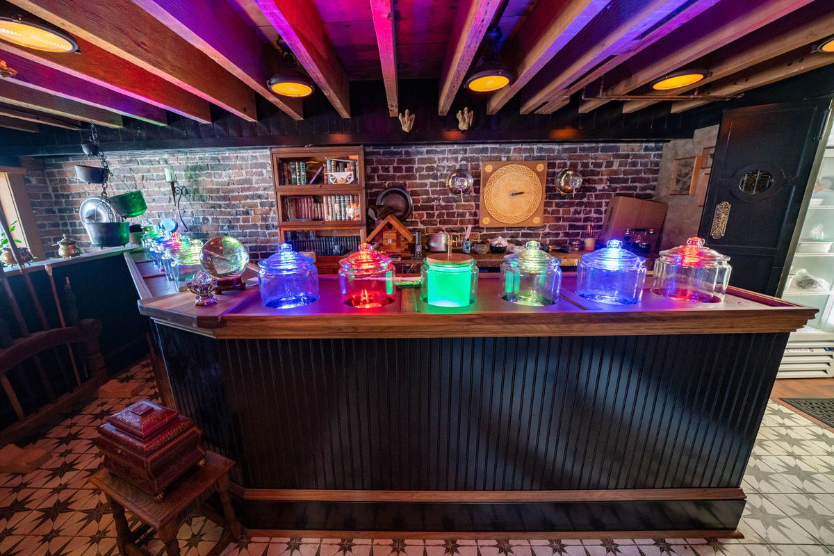 The wand bar at the Splintered Wand with various vessels lit up in different colors.