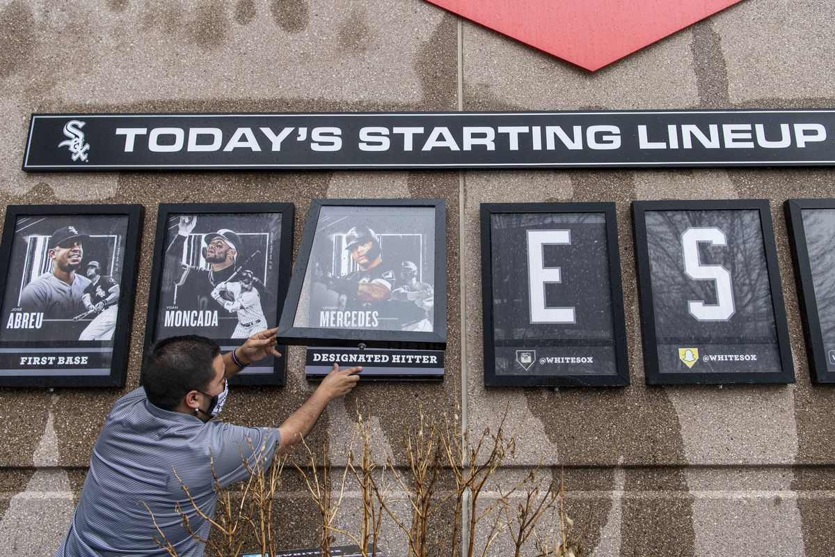 Chicago White Sox staff member, Michael Gomez adds a photo of Yermin Mercedes to a starting lineup board outside Guaranteed Rate Field before the Chicago White Sox home opener, Thursday, April 8, 2021.