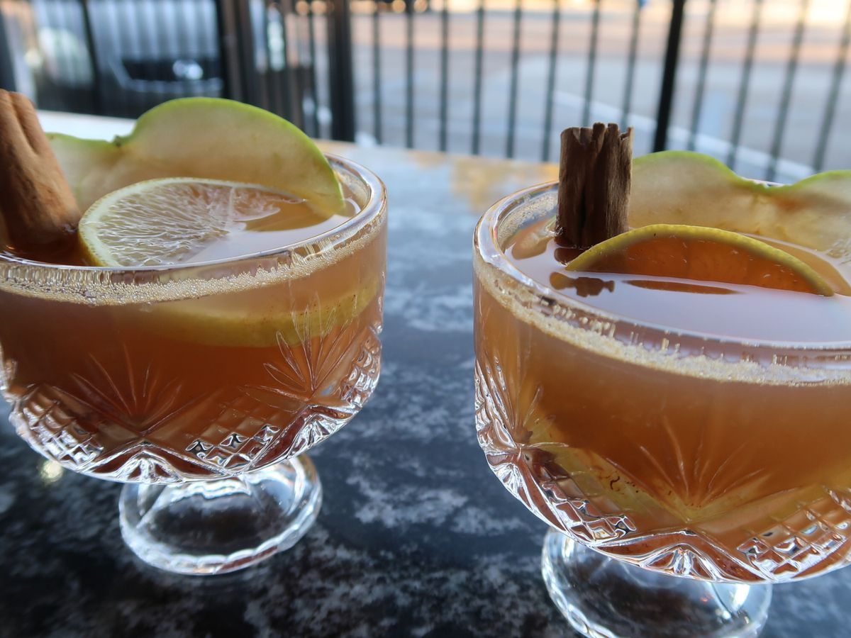 two hot toddies on a table outside, garnished with cinnamon sticks and lemons