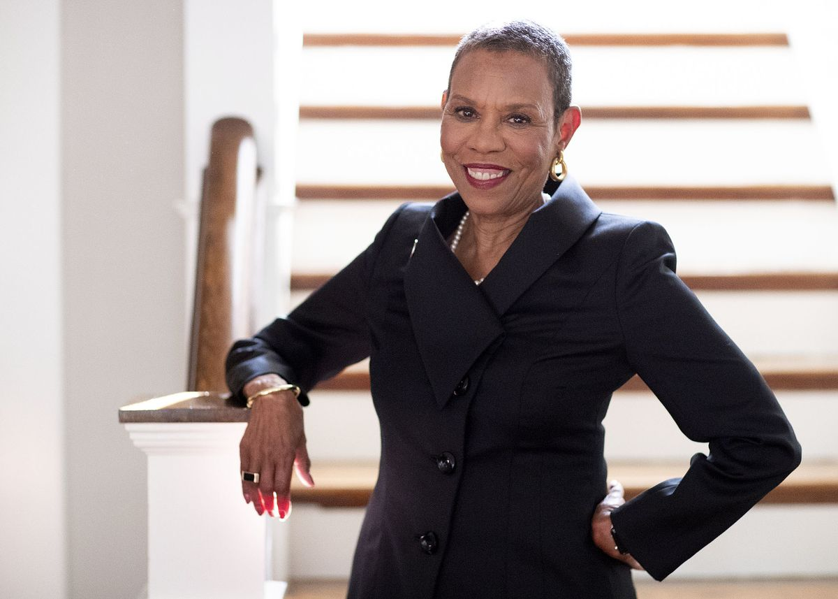 A woman in a black business suit stands in front of stairs.