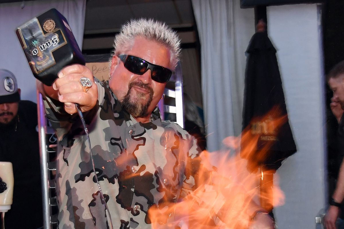 Guy Fieri pouring alcohol on a flame.