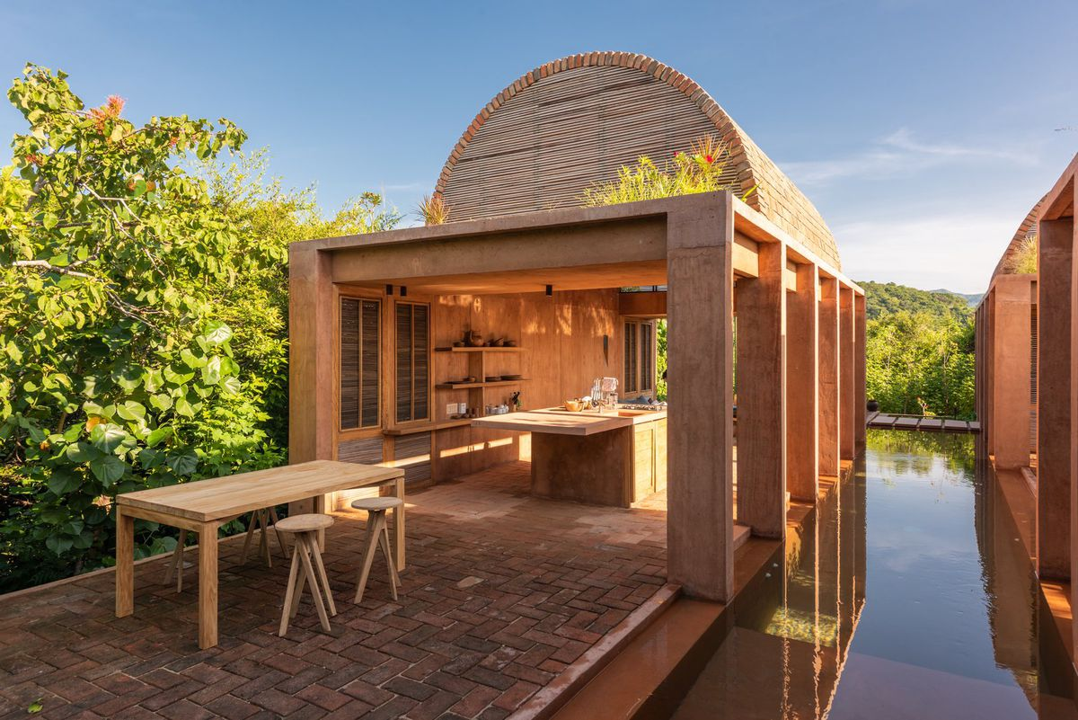 A vaulted, open-air kitchen on a brick terrace next to a moat. A wooden table sits on the brick patio.