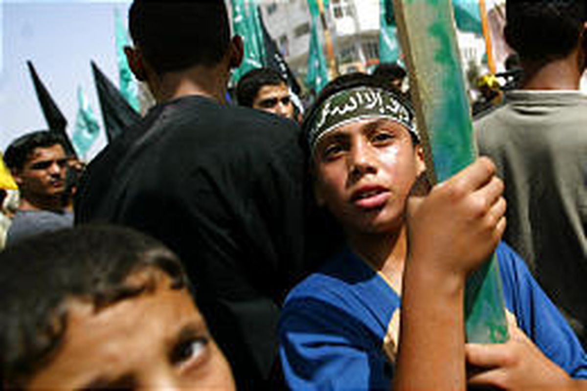 A boy wears a headband and carries a flag at a small pro-Yasser Arafat rally in Buerij, Gaza Strip, Friday.