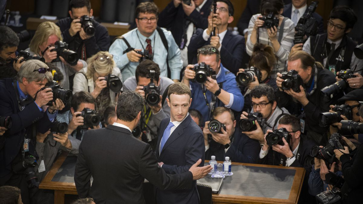 Facebook CEO Mark Zuckerberg surrounded by reporters and photographers at a Senate hearing.