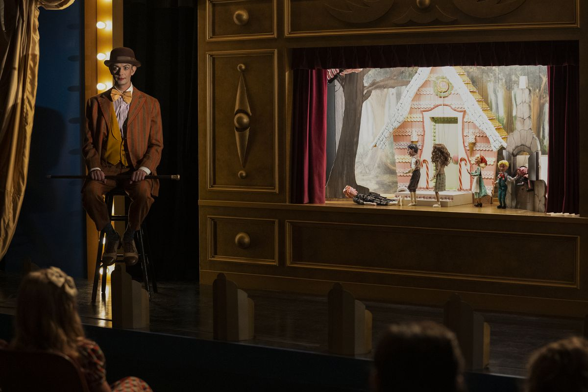 A man in vaudeville makeup sits on a stage with a brightly lit marionette show in Ratched