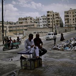 In this Tuesday, Sept. 11, 2012, photo, Syrian men chat while others walk past a pile of garbage left on a roadside in Aleppo, Syria. The days are still hot across the fertile plains of northern Syria, but at night there is a hint of a chill an ominous harbinger of winter's approach and the deepening of the humanitarian crisis gripping a country wracked by civil war.