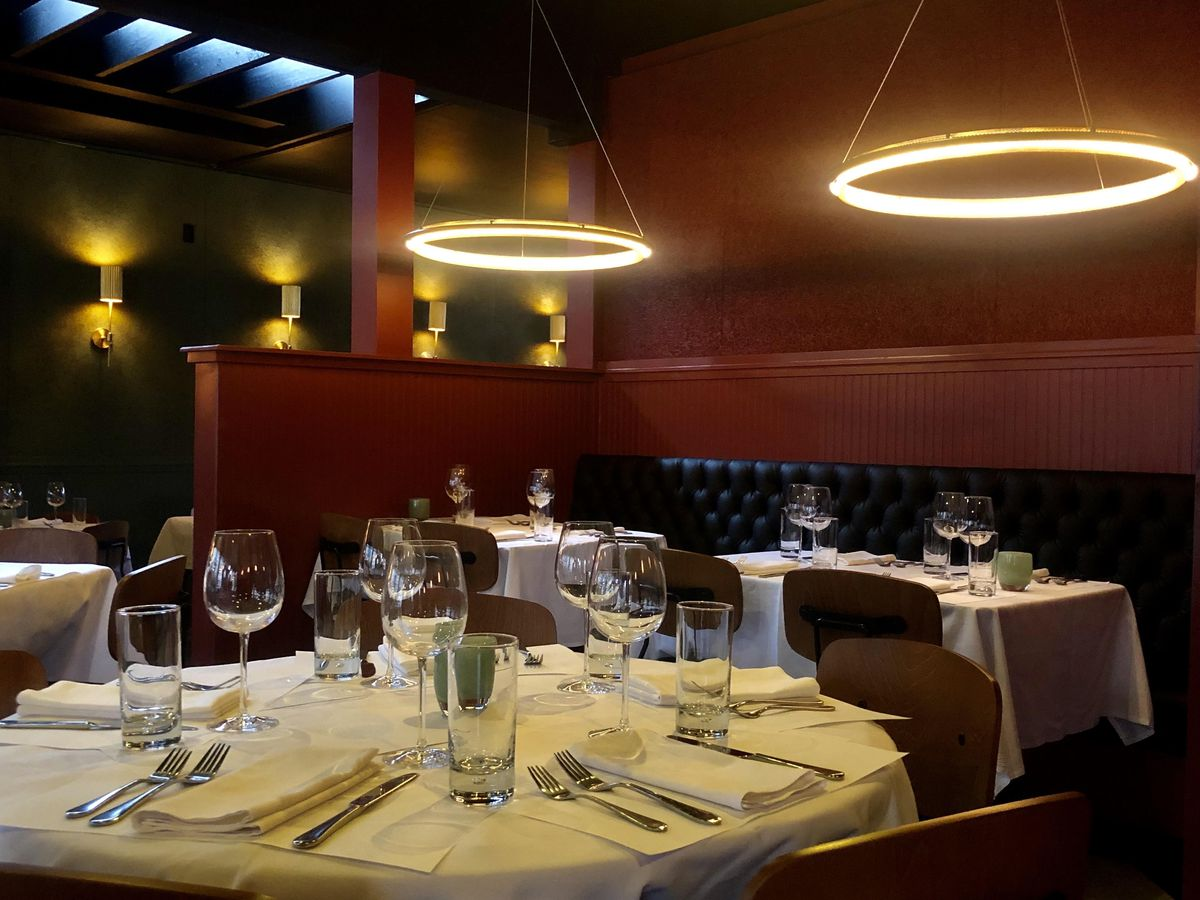 Serafina's revamped dining room, with halo-like lamps and cushioned leather banquettes.