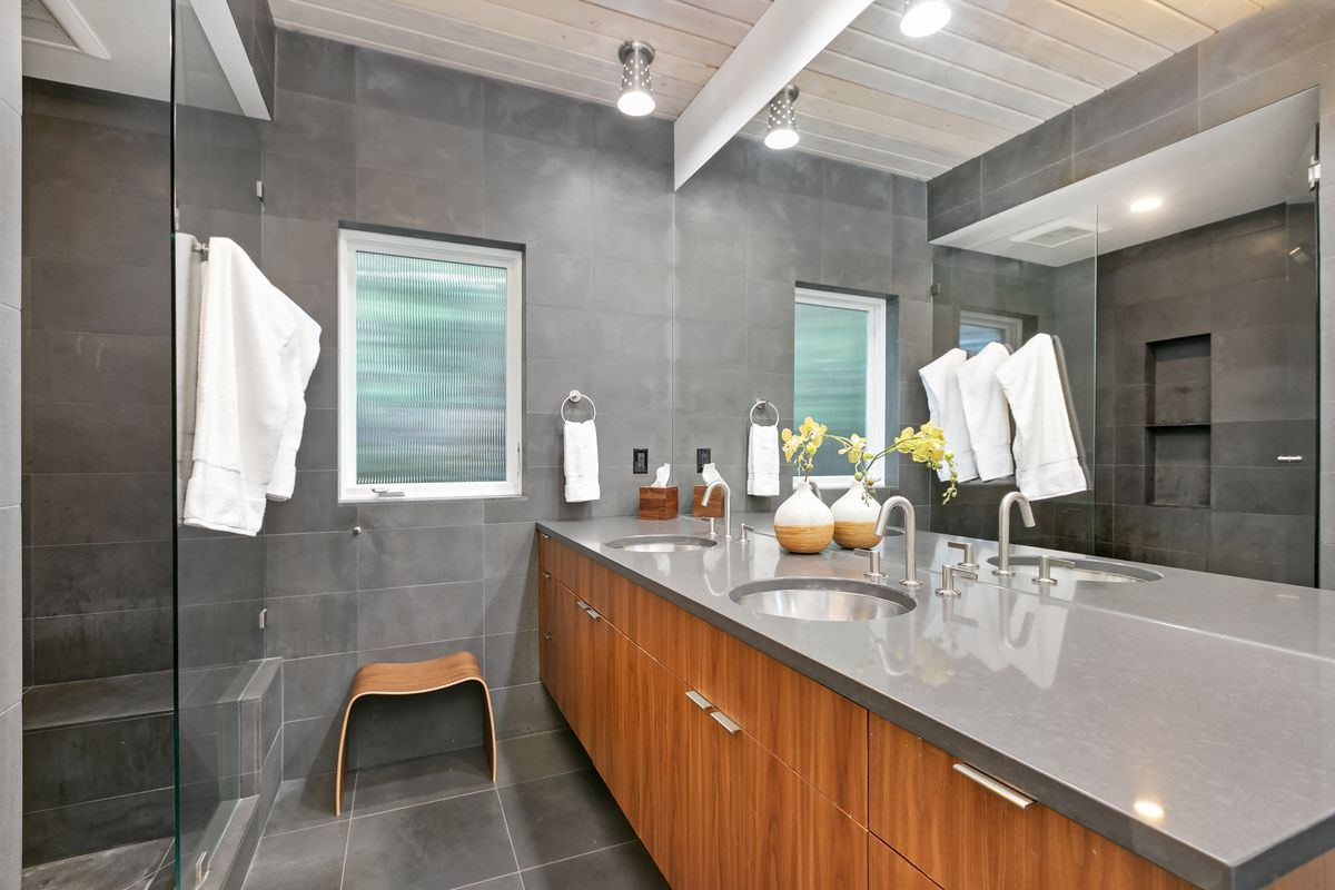 A master bathroom has two sinks, walnut cabinets, gray counters, gray walls, and a glass shower.
