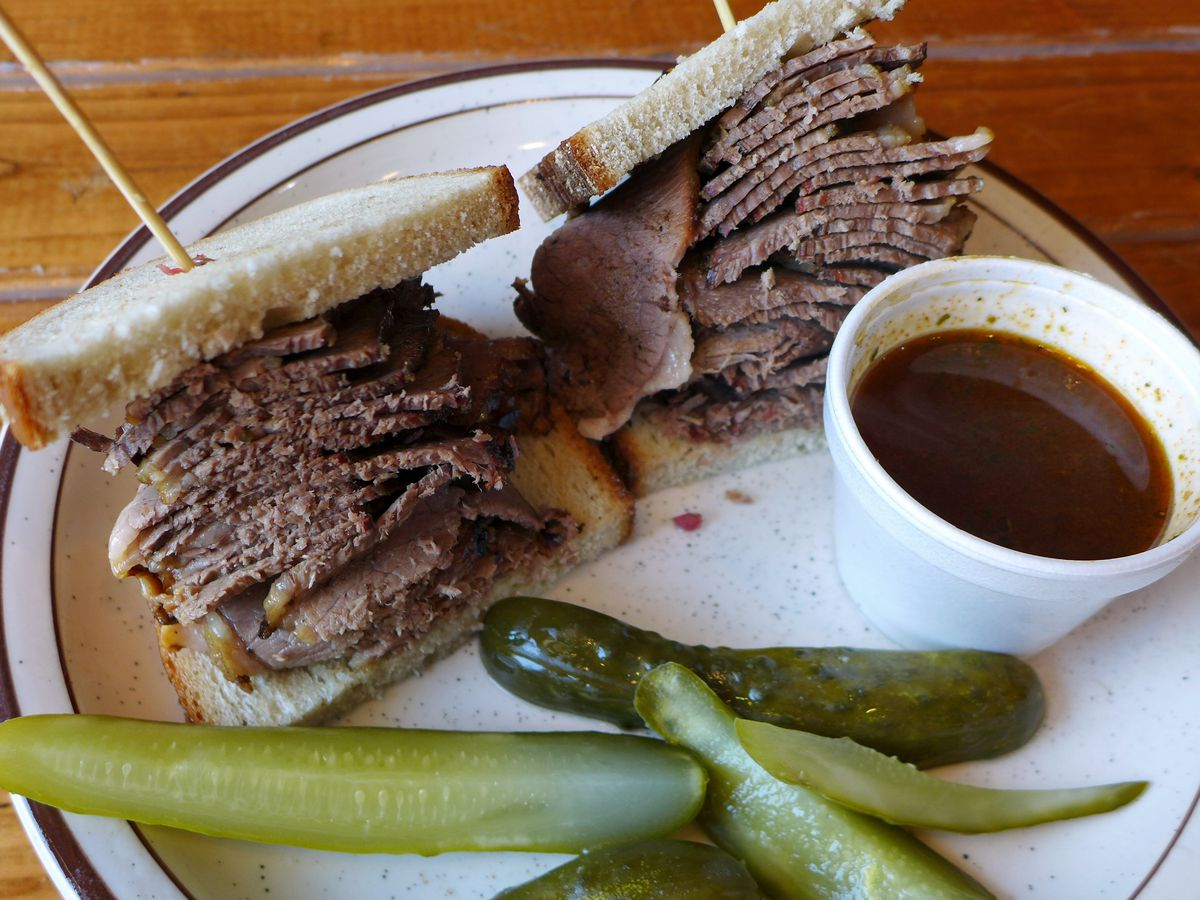 A meat-filled sandwich with pickles and a cup of gravy on the side.