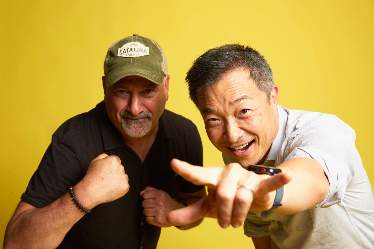 Dan DiDio, in trucker cap and t-shirt, pumps his fist while Jim Lee makes a two-fingered hang-loose salute for the camera.