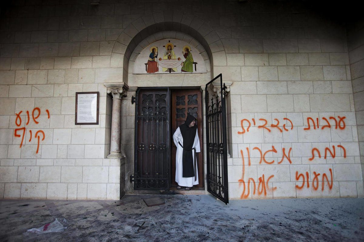 FILE- In this Sept. 4, 2012, file photo, a Catholic monk stands in a doorway of the Latrun Trappist Monastery where Israeli police say vandals spray-painted anti-Christian and pro-settler graffiti and set the monastery's door on fire, in Latrun, between J