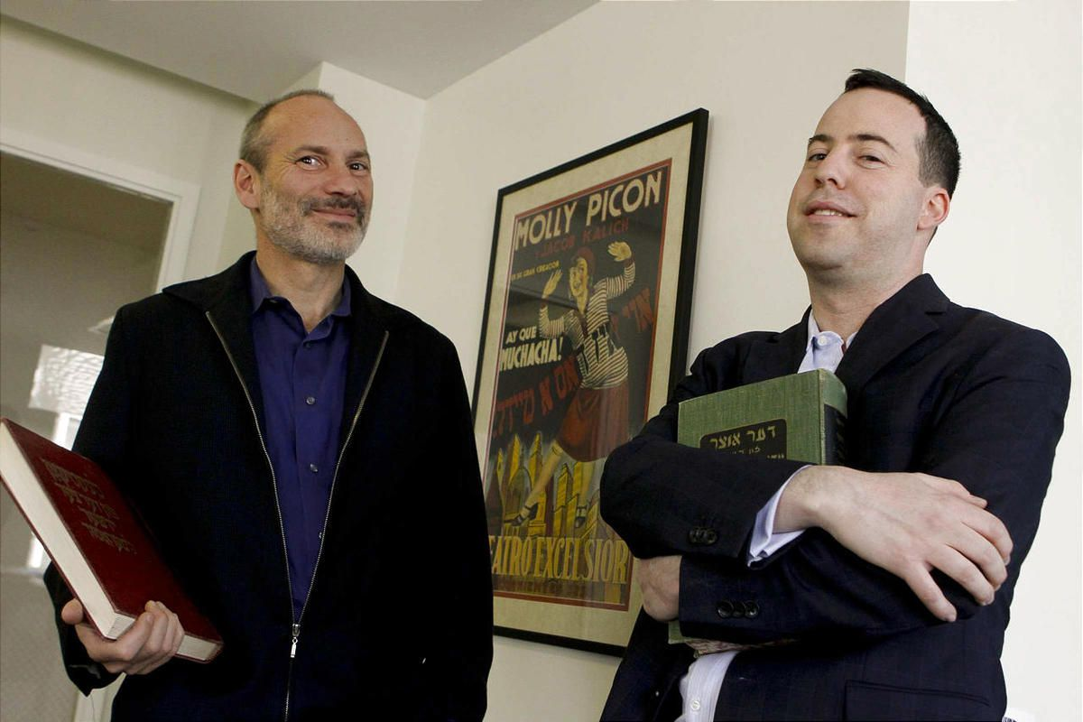 Robert Adler Peckerar, right, executive director of Yiddishkayt and Aaron Paley, founder of Yiddishkayt, pose for a portrait in the Yiddishkayt office with a vintage Yiddish poster in Los Angeles, California, April 3, 2012. (Anne Cusack/Los Angeles Times/