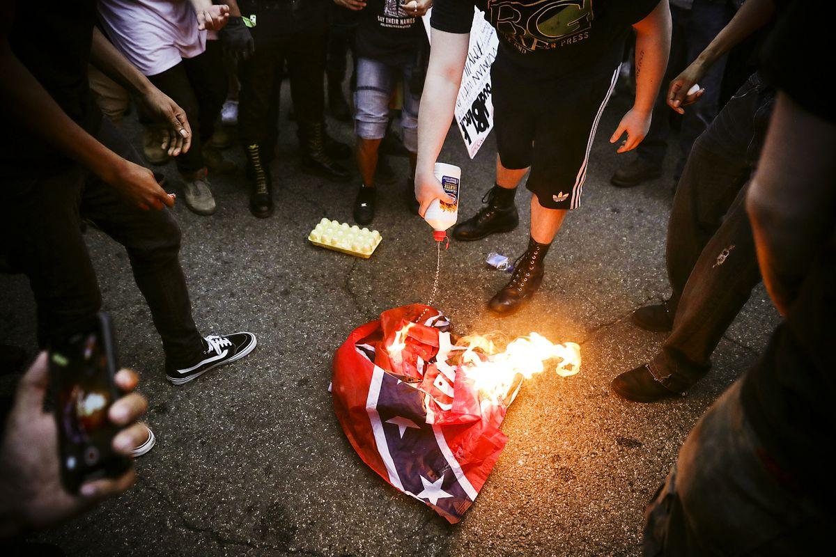 Members of the Antifa and Blac Bloc burn a Confederate battle flag near Lafayette Square park.