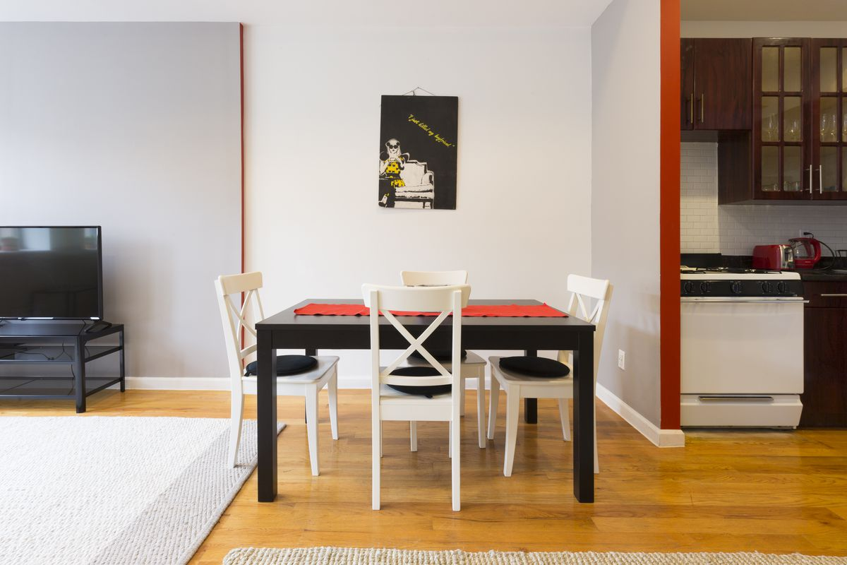 A dining area with a table and four chairs.