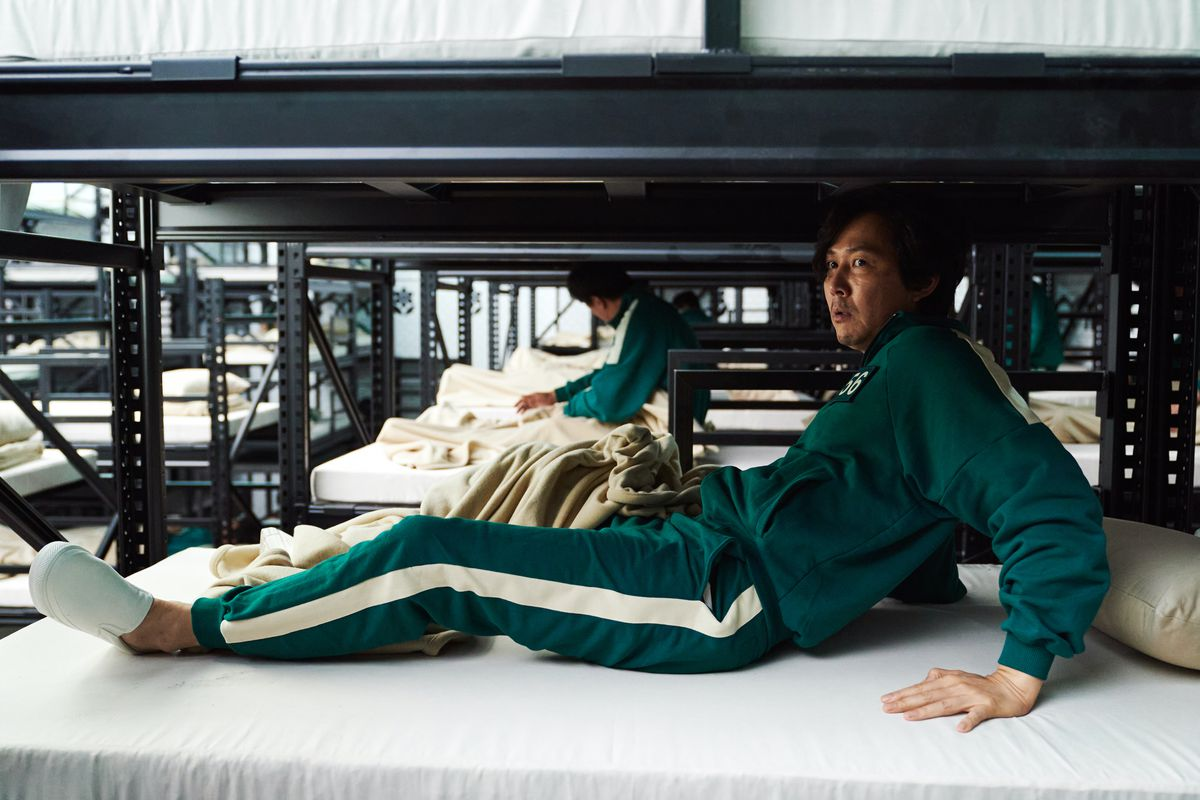Squid Game protagonist Seong Gi-hun sits up in a bunk, looking startled, in an early episode of Squid Game