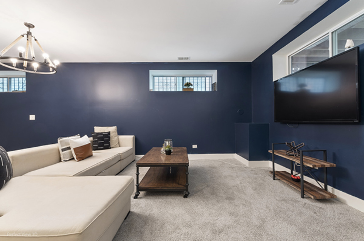 The finished basement with a tv, navy blue walls, and a large sectional couch.