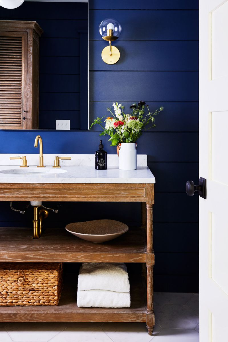 A white sink with open bottom shelving sits in front of a dark blue shiplap wall. On top of the marble counter top sits a bouquet of fresh flowers in a milky white painted mason jar. In the open cabinets below the sink a bowl, white towels, and a brown woven basket are visible. A plain rectangular mirror is hung behind the sink.
