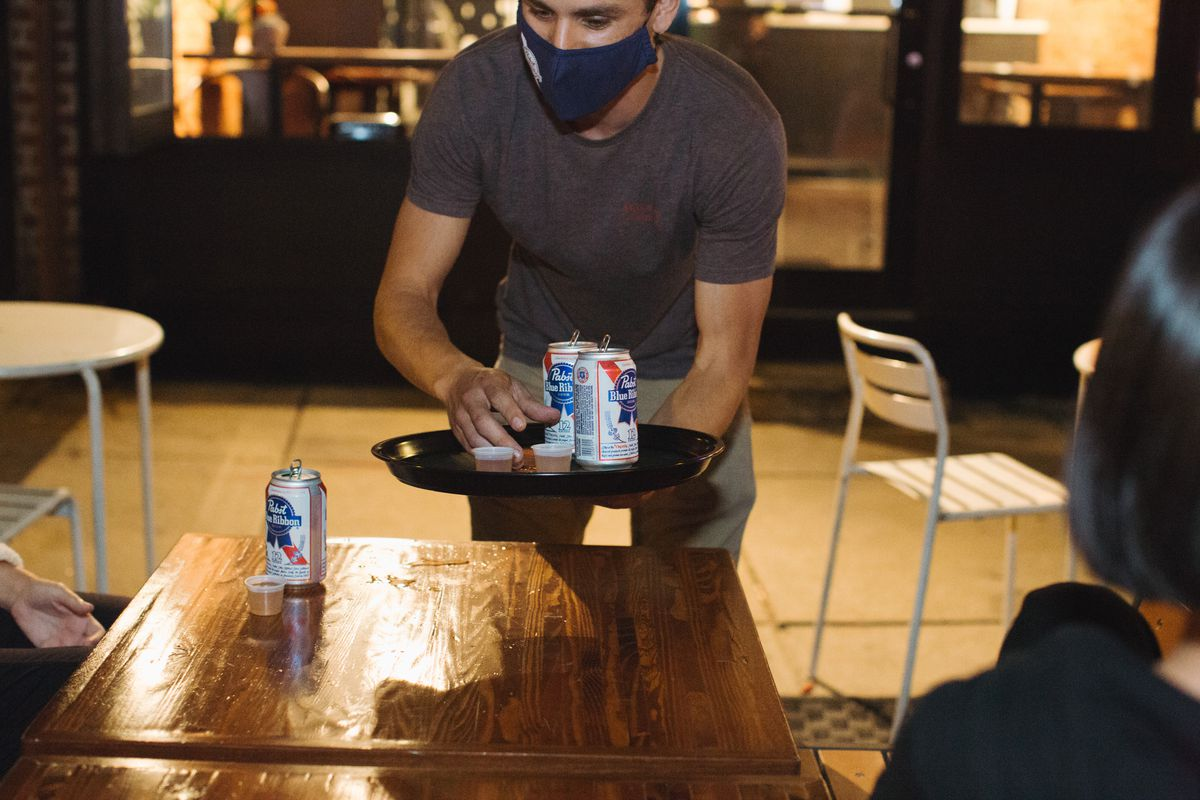 a server wearing a pandemic face mask with a tray of beer cans