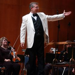 Sterling Poulson motions to the Choral Arts Society of Utah and the Days of '47 Orchestra while the audience applauds at the Days of '47 Pops Concert held at Abravanel Hall, Monday, July 8, 2002.