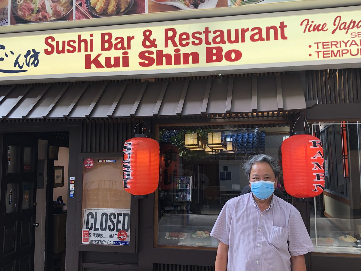 William Lee, in a blue face mask, stands in front of the facade of Kui Shin Bo restaurant
