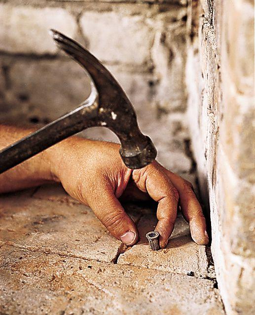 Person hammering nail into brick.
