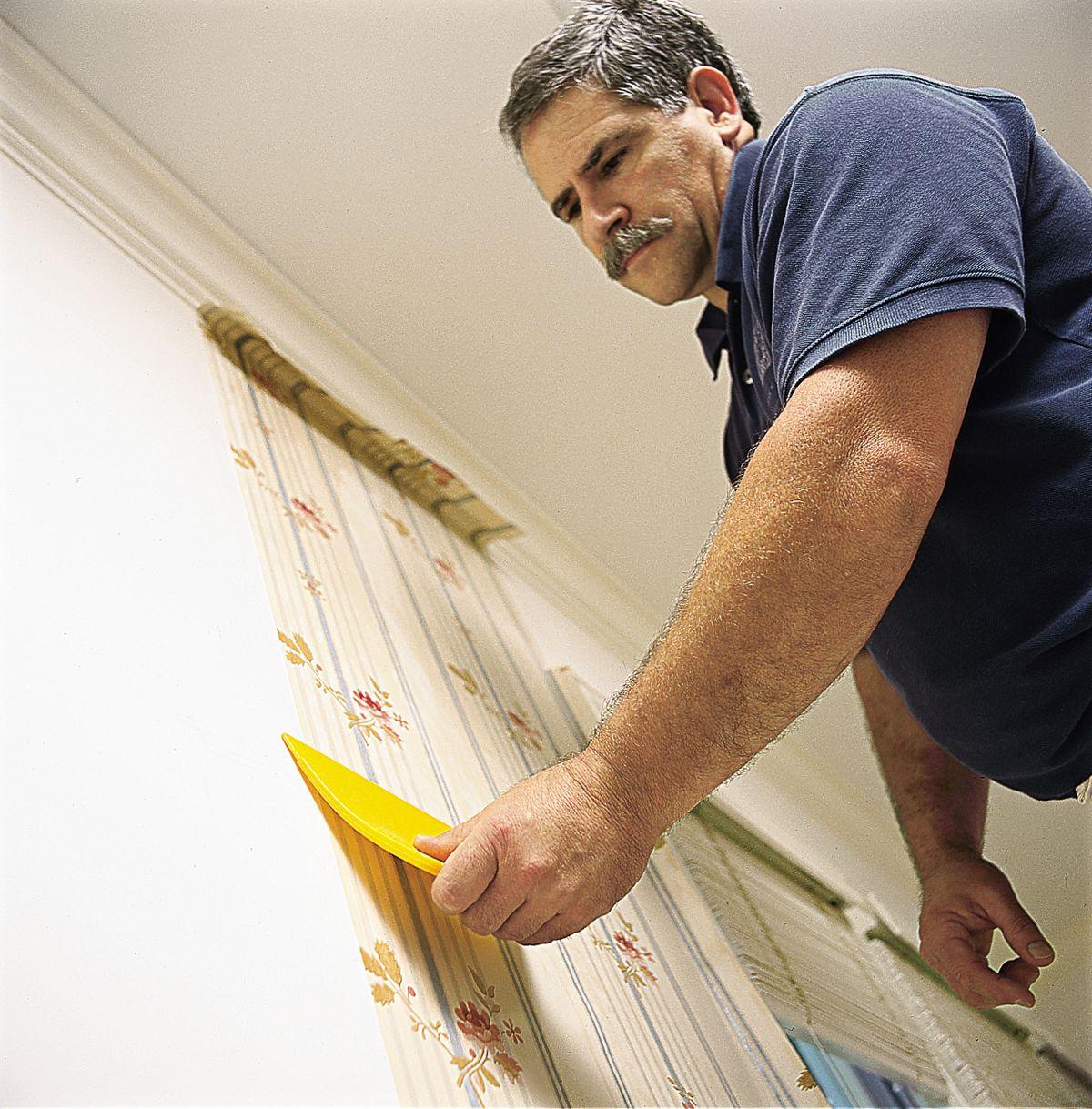 Man Hanging First Strip Of Wallpaper
