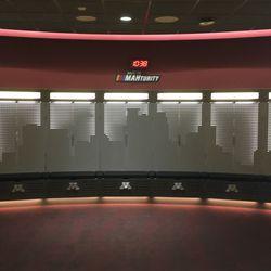 The lockers in the football locker room  show the Minneapolis skyline