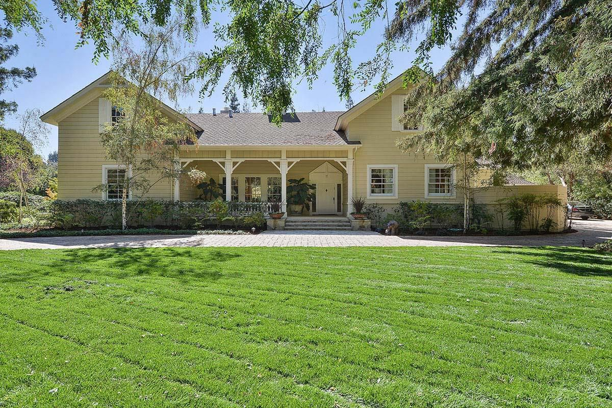 Exterior of 1912 home in Atherton. Beige exterior. Gorgeous massive lawn.