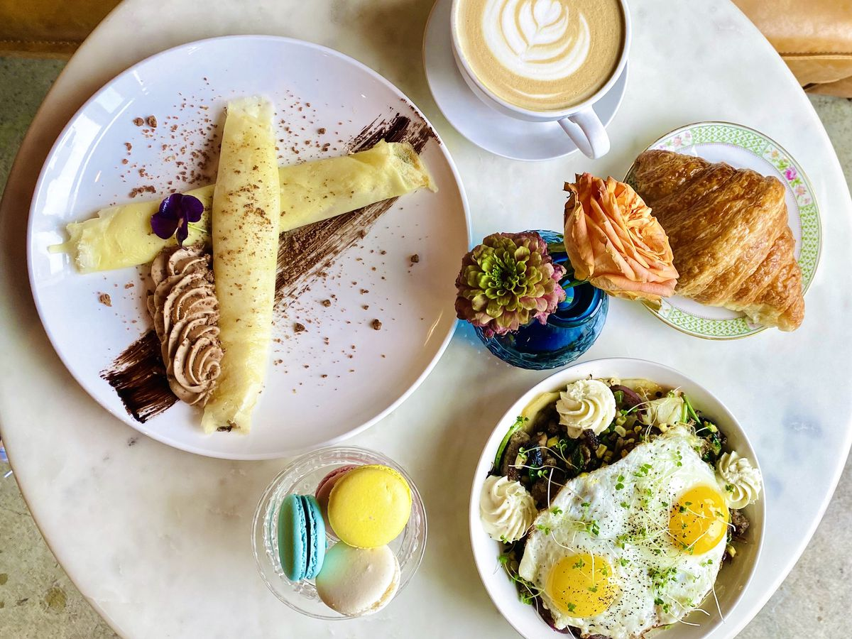 From above, a small table filled with brunch plates, including a croissant, an omelet with decorative flourishes, macarons, and a breakfast bowl topped with eggs
