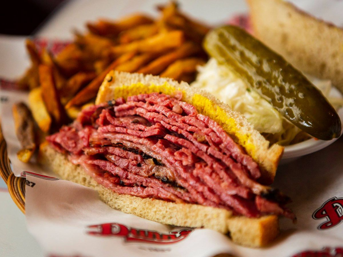 Half of a smoked meat sandwich with mustard on rye.