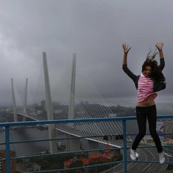 A woman jumps as she poses for a picture in front of a cable-braced bridge in the eastern Russian city of Vladivostok Wednesday, Sept. 5, 2012. Once a mysterious closed city during Soviet times, Vladivostok is ready to strut in the world spotlight as host of the Asia-Pacific Economic Cooperation summit. Russia has splashed $20 billion preparing for the summit in Vladivostok, its largest but long-neglected Pacific port, as part of a grand plan to become a bigger player on Asian markets.