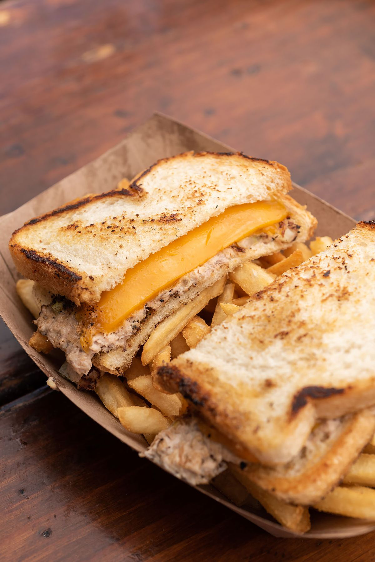 A tuna melt with partially-melted American cheese on a wooden table.