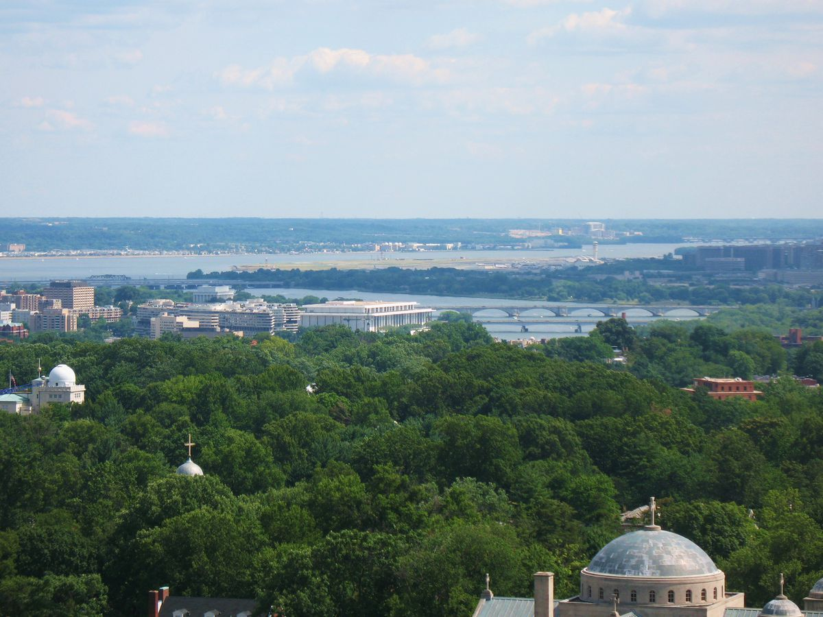 An aerial view of the Washington National Cathedral. The top of the building is a dome shape. There are trees and a body of water in the distance.