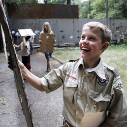Cole Norton checks out his target after practicing his aim at the firing range during activity time at Camp Tracy in Mill Creek Canyon on Friday, July 22, 2016.