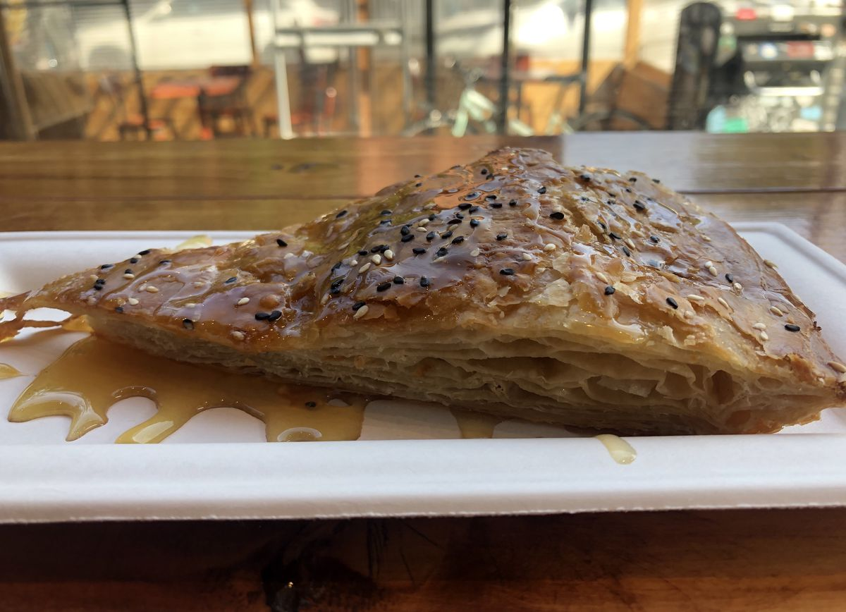 A slice of pastry with layers of dough and topped with sesame seeds and honey is on a rectangular white plate sitting on a wooden table