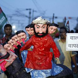 """Samajwadi Party activists hold an effigy representing Indian Prime Minister Manmohan Singh and his cabinet colleagues before burning it during a protest along railway tracks in Allahabad, India, Thursday, Sept. 20, 2012.  Angry opposition workers have disrupted train services as part of a daylong strike in India to protest rising diesel prices and the government's decision to open the country's huge retail market to foreign companies. Placard reads """"Take Walmart back."""""""