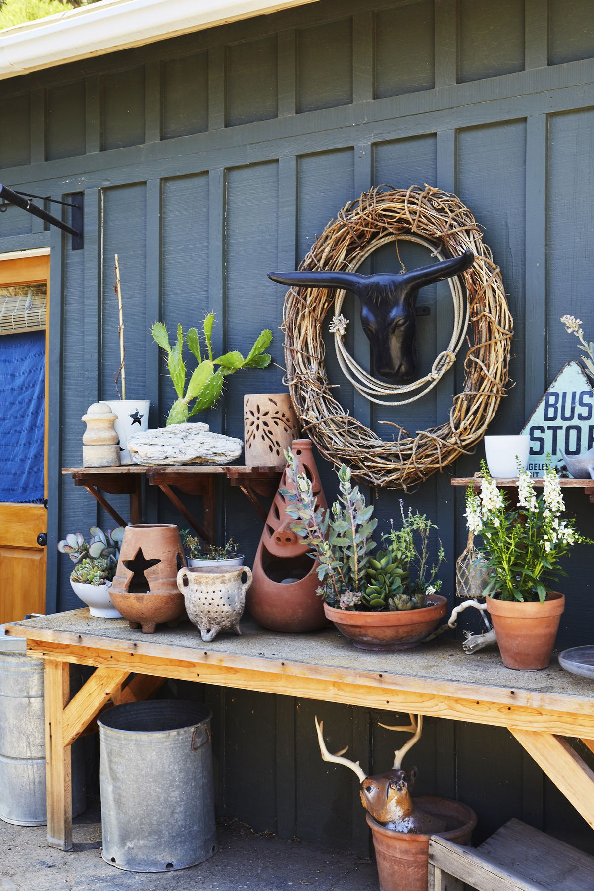 A potting-type area filled with plants and pots sits outside a blue guest cottage.