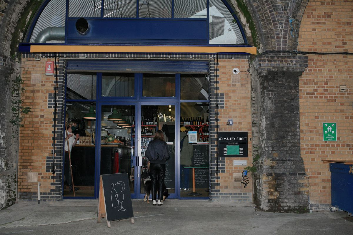 The front of London restaurant 40 Maltby Street, a blue arched entrance with bricks and a blackboard outside