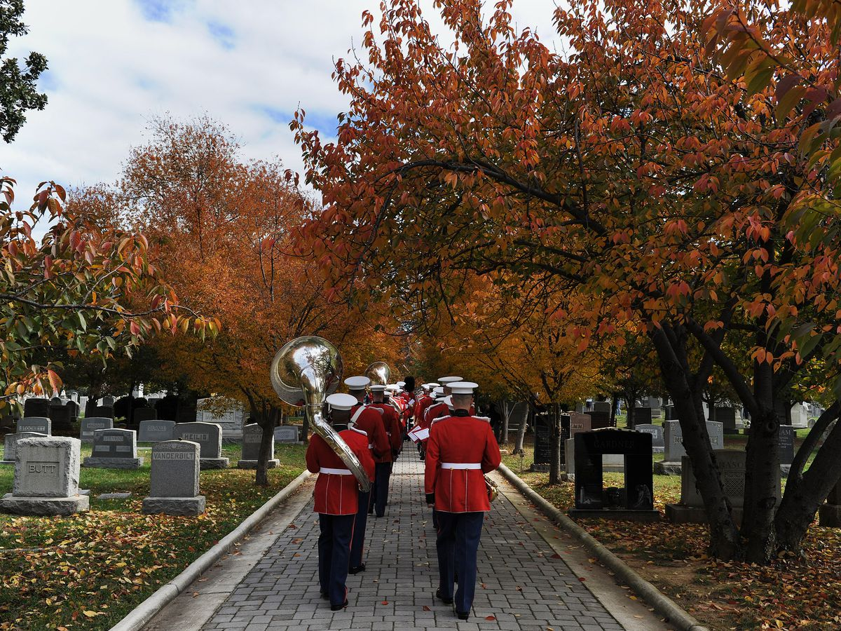 Men in red band uniforms holding instruments walk through a cemetery during the fall.