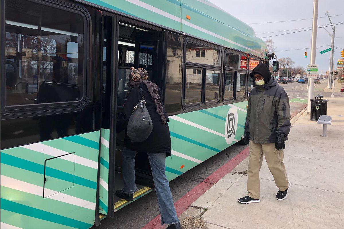 """Two people enter a greet and white bus with a big """"D"""" on the side. One wears a face mask."""