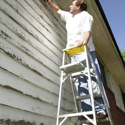 Scott Anderson, CEO of Zions Bank, scrapes wood on a house to prepare for painting as a service project.