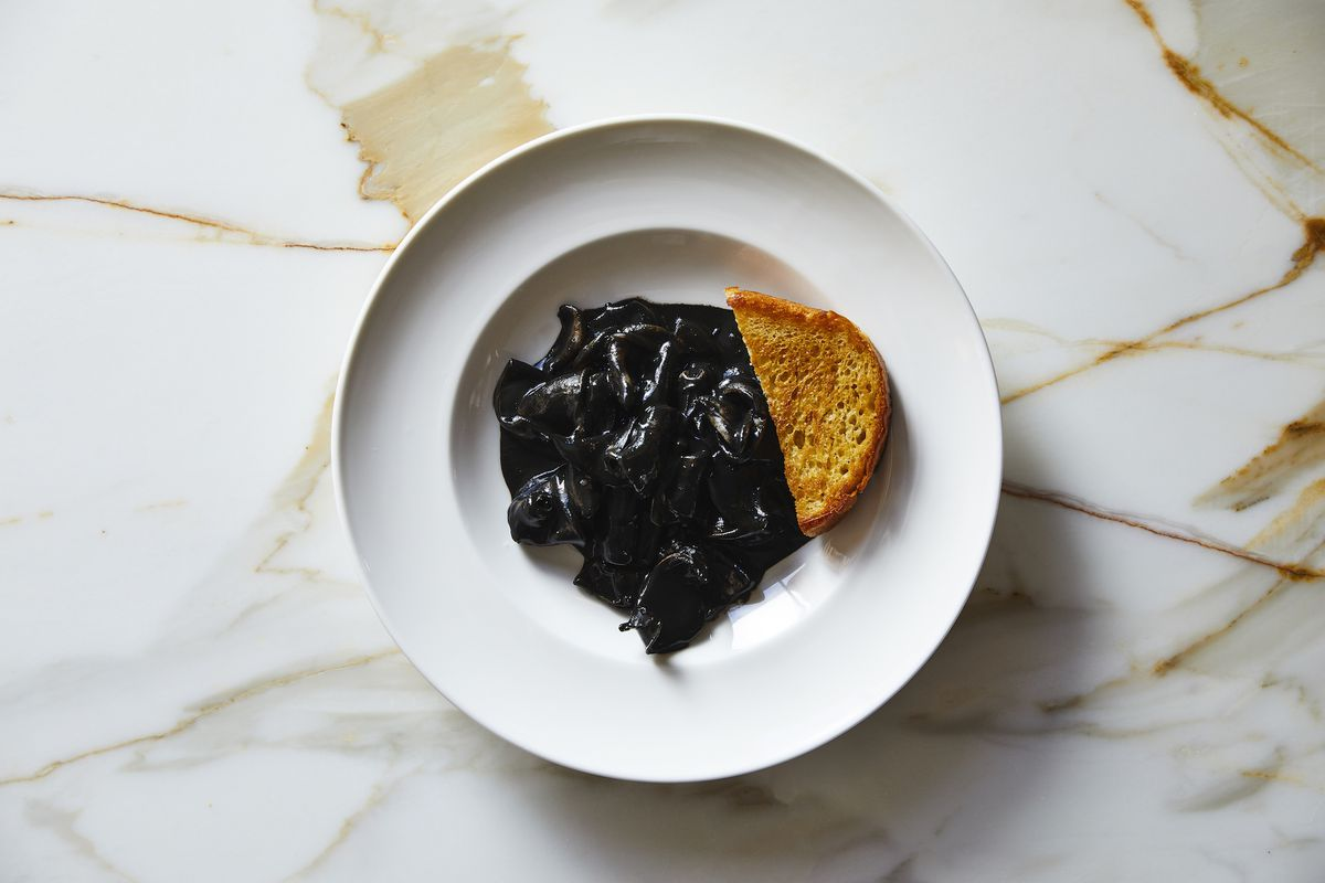 A white bowl on a marble table with a piece of toast and calamari with black squid ink in it
