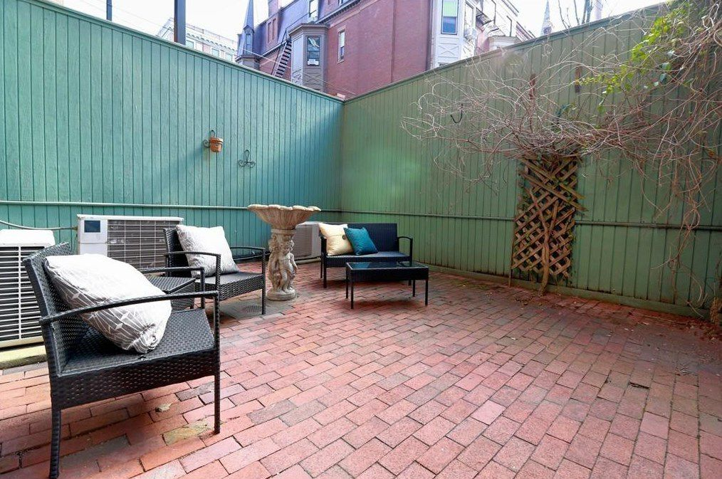 A brick patio with furniture and enclosed by high green walls.